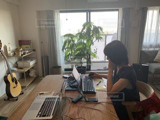 ラップトップコンピュータを使ってテーブルに座っている人の写真・画像素材[3257663]