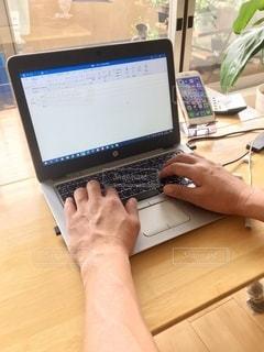 木製のテーブルでラップトップコンピュータを使っている人の写真・画像素材[3329049]