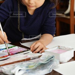 テーブルに座っている小さな女の子の写真・画像素材[2259889]