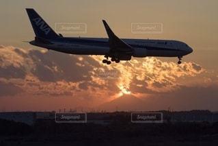 曇った空を飛ぶ大型旅客機の写真・画像素材[3400993]