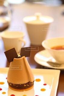 ケーキの皿とコーヒーを一杯の間に近づけての写真・画像素材[3860426]