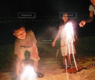 夜のビーチで子ども花火の写真・画像素材[3610807]