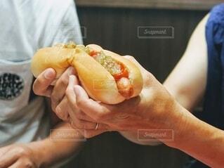 食べ物,手,パン,手持ち,人物,食品,おいしい,ポートレート,ホットドッグ,ホット,ライフスタイル,手元,割る,はんぶんこ,分ける,ちぎる