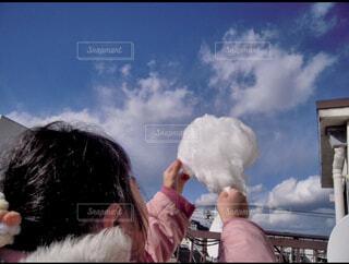 子ども,空,屋外,雲,女の子,手持ち,人物,人,ポートレート,ライフスタイル,願い,手元,綿菓子,クラウド,わたあめ