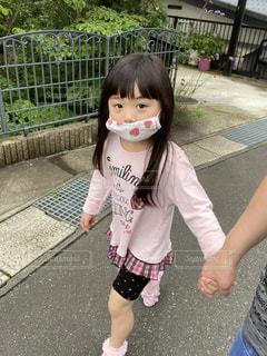 フェンスの隣に立っている少女の写真・画像素材[3526676]