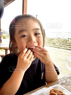 食べ物を食べるテーブルに座っている人の写真・画像素材[3759604]