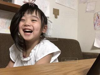 テーブルの上に座っている女の子の写真・画像素材[4322211]