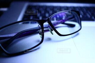 パソコンのキーボードの上に乗せたメガネの写真・画像素材[3761656]