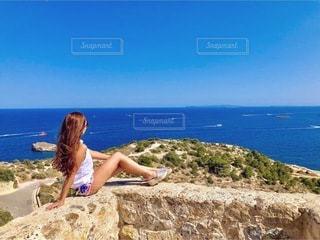 海の近くの岩の上に座っている女性の写真・画像素材[3290835]