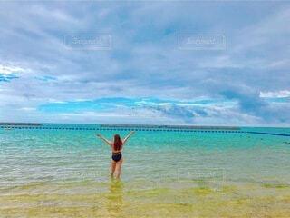 水の体の隣に立っている男の写真・画像素材[3825734]