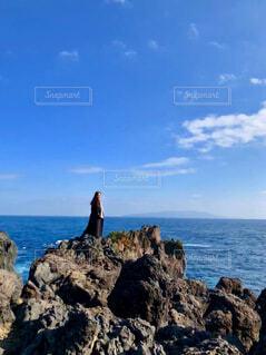 岩場のビーチに立つ人々のグループの写真・画像素材[3840372]