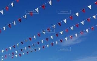青い空に紅白の旗の写真・画像素材[3350243]