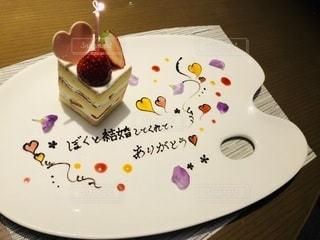 テーブルの上に座っているチョコレートケーキをトッピングした白い皿の写真・画像素材[3307281]