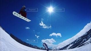 雪の板に乗って空を飛んでいる男の写真・画像素材[3314094]