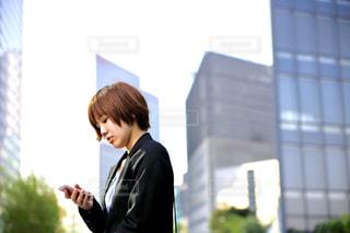 携帯電話で話している建物の前に立っている女の写真・画像素材[746988]