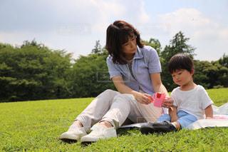 草の上に座っている男にフィールドが覆われています。の写真・画像素材[748870]