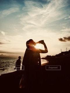 夕日の前のビーチに立っている人の写真・画像素材[3410688]