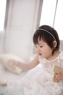テーブルの上に座っている小さな女の子の写真・画像素材[3352111]