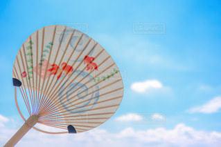 うちわと夏空の写真・画像素材[3554528]
