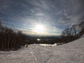 雪に覆われた斜面の下にスノーボードに乗っている男の写真・画像素材[3388637]