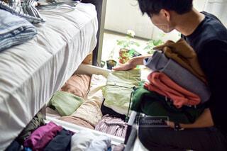 窓際で衣替えをして、シャツを手に取る男性の写真・画像素材[4375575]