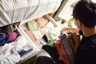 ベッドの横で衣替えする男性の写真・画像素材[4375582]