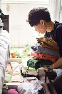 窓際のベッド下収納から冬服を取り出し衣替えする男性の写真・画像素材[4375584]