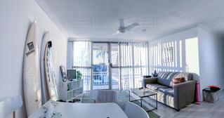 家具とサーフボードと大きな窓のある海外の白い部屋の写真・画像素材[4409947]