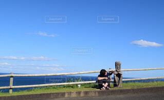 夏空の下石の人形の隣に座る女性の写真・画像素材[4431606]