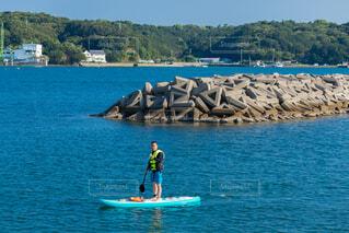 港の海面でサップボードをしている男性の写真・画像素材[4872292]