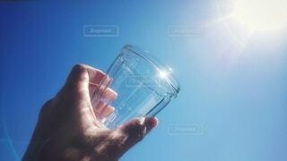 空,屋外,太陽,青,青い空,手,反射,ガラス,手持ち,コップ,人物,グラス,ポートレート,ライフスタイル,手元,持つ,掲げる,透明な材料