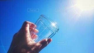 空,屋外,太陽,青,青い空,手,反射,ガラス,光,手持ち,コップ,人物,グラス,ポートレート,ライフスタイル,手元,持つ,掲げる,透明な材料