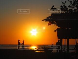 ビーチに沈む夕日と、カップルの写真・画像素材[3404077]