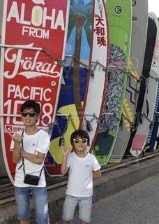 サーフボードの前に立つ男の子の写真・画像素材[3422997]