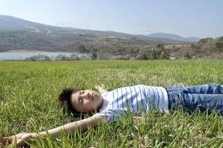 芝生の上に横たわる少年の写真・画像素材[3424060]