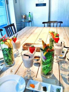 テーブルの上の野菜サラダといちごシェイクの写真・画像素材[4331331]