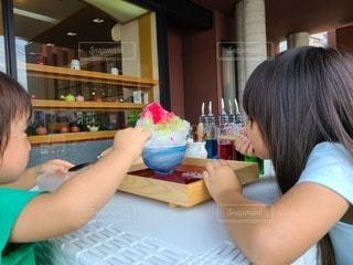 テーブルに座っている小さな女の子の写真・画像素材[3588746]