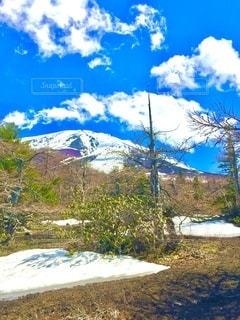 真っ青な空と白い雲が眩しいまだ残雪残る山の景色の写真・画像素材[3634185]