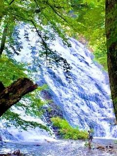 大迫力の滝の絶景を前に、川に入って1人で釣りを楽しむ男性の写真・画像素材[3634368]