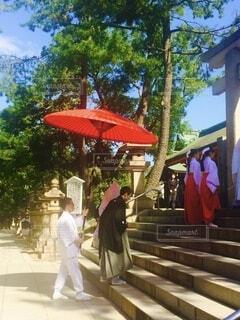 真っ赤な和傘をさして貰い、神社への階段を上がる新郎新婦の写真・画像素材[3671903]