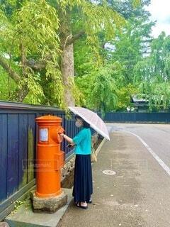 昭和レトロな赤いポストに手紙を出すピンク傘の女性の写真・画像素材[3672776]