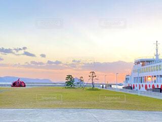夕暮れ時が美しい直島の赤かぼちゃとフェリーの写真・画像素材[4014478]