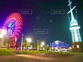 芝生とベンチの公園、ライトアップされた観覧車と灯台とホテルの写真・画像素材[4071079]