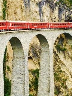 アーチ型の石橋を走行中の真っ赤な観光列車のクローズアップの写真・画像素材[4453935]