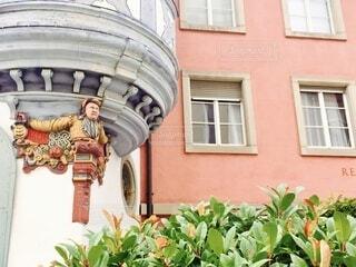 カラフルな男性の彫刻が施されたピンクの古い建築物と緑の植物の写真・画像素材[4459624]