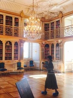 豪華なシャンデリア、優しい日差し差込む図書室を歩く若い女性の写真・画像素材[4460376]
