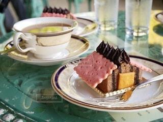 緑色の卓上、ピンク屋根の家型ケーキと表面に新緑が映る紅茶の写真・画像素材[4587872]