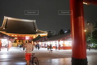 ライトアップされた浅草寺、自転車を押す1人の男性の後ろ姿の写真・画像素材[4642116]