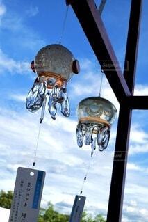 夏の青空を背景に、2つの透明なクラゲ風鈴のクローズアップの写真・画像素材[4712798]