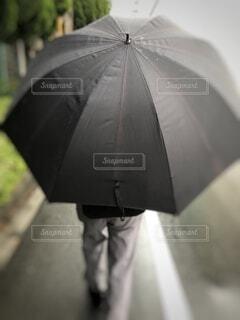 傘をさして歩く男性の写真・画像素材[3690917]